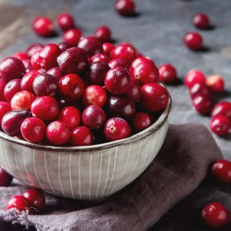 A bowl cranberries sitting on a table.