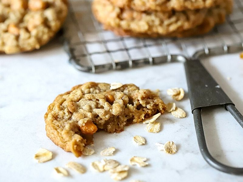 An oatmeal cookie with a bite out of it.