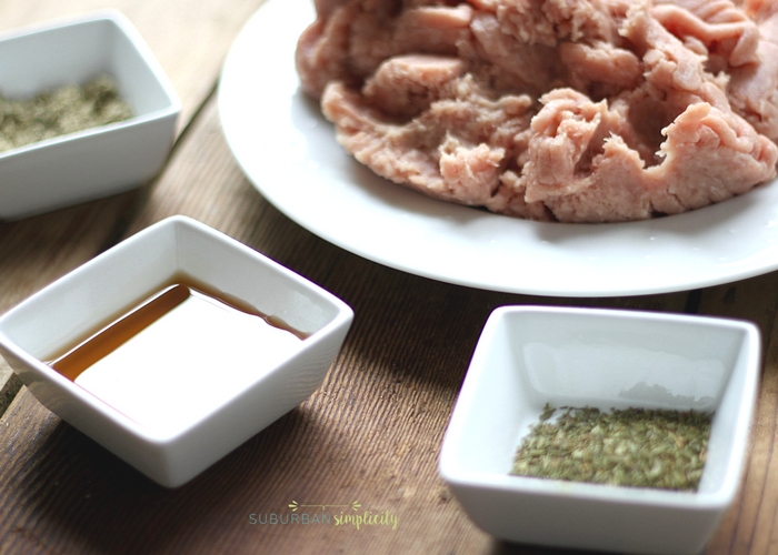 Ingredients including raw meat, maple syrup and dried herbs to make homemade maple sausage.