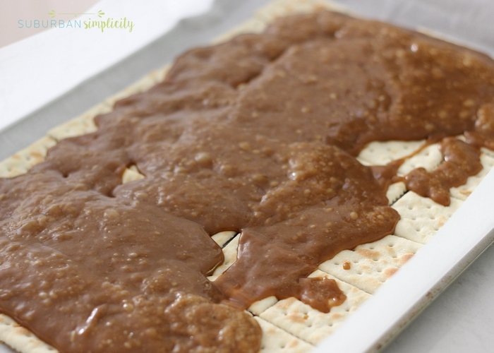 saltine toffee with hot caramel being poured on top.