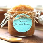 Vanilla Brown Sugar Scrub in a jar with a wooden spoon next to it. It has a homemade tag tied on with twine.