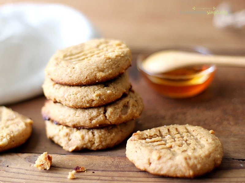 Paleo Peanut Butter Cookies are healthy cookies on a counter with honey in the background.