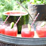 Watermelon Punch with stripped straws in a serving tray