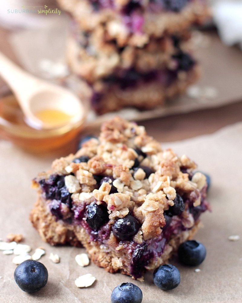 Blueberry Oatmeal Bars on the counter with fresh blueberries all around as well as honey in the background.