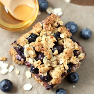 Blueberry oatmeal bar with honey next to it.