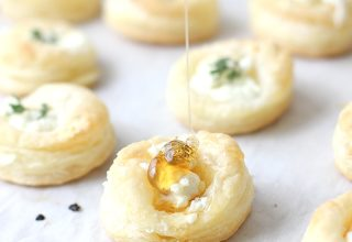 Goat cheese and honey bites with honey being dripped on them.