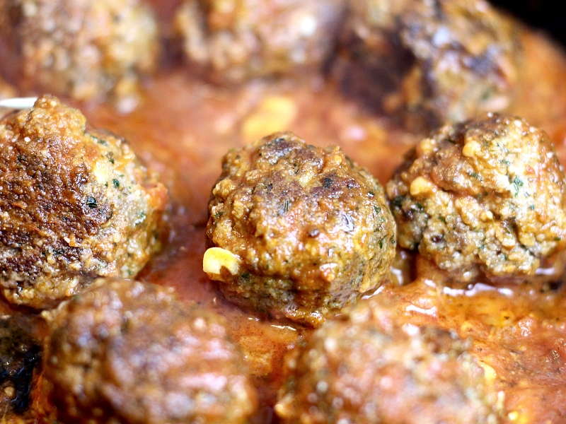 Italian Meatball appetizer in a skillet with marinara sauce.