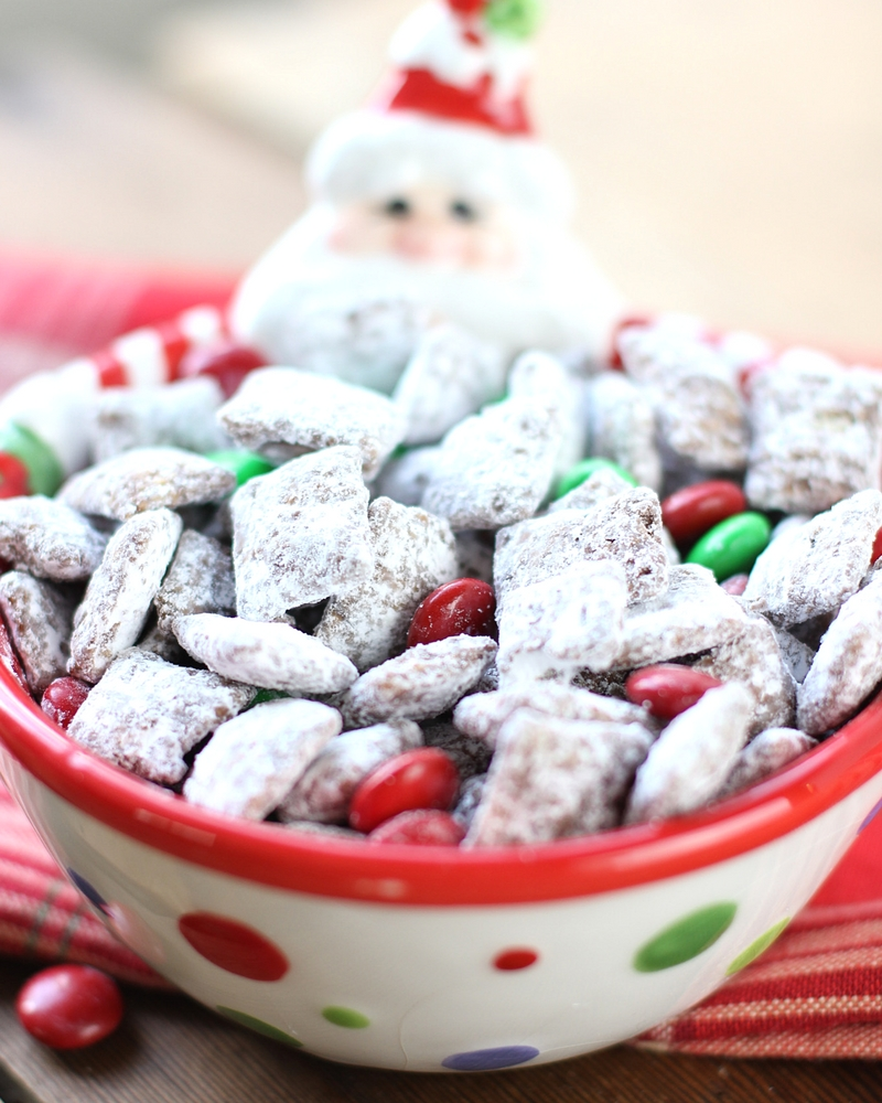 Reindeer Chow Muddy Buddies in a polka dotted bowl with Santa peeking over the top. You can see red and green M&Ms