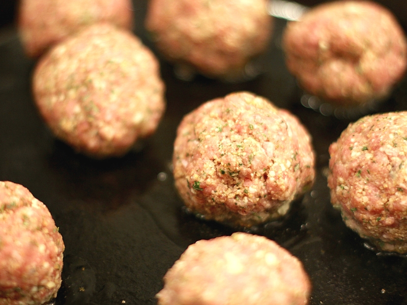 Meatball Parmesan Bites cooking in a skillet.