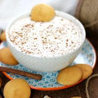 Egg nog dip in a bowl on a plate surround by vanilla wafter cookies and a cinnamon stick.
