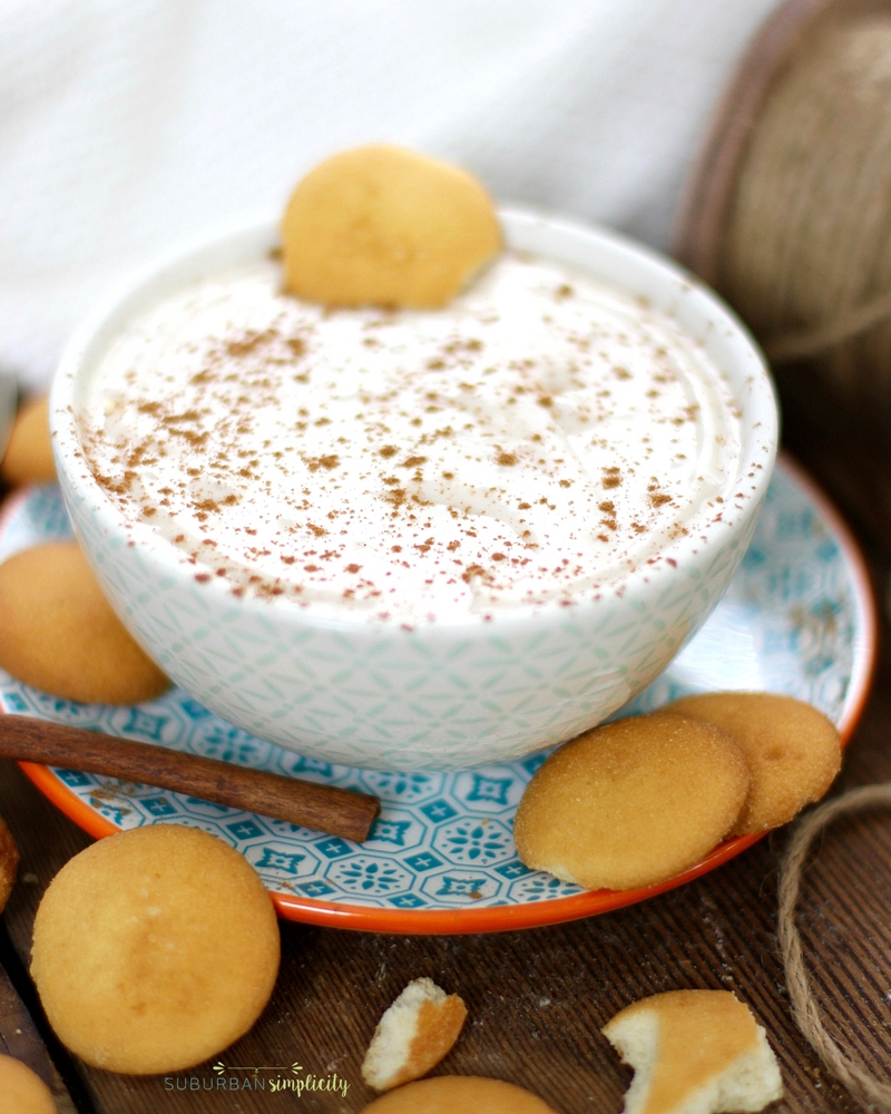 Eggnog dip in a bowl on a plate surround by vanilla wafter cookies and a cinnamon stick.