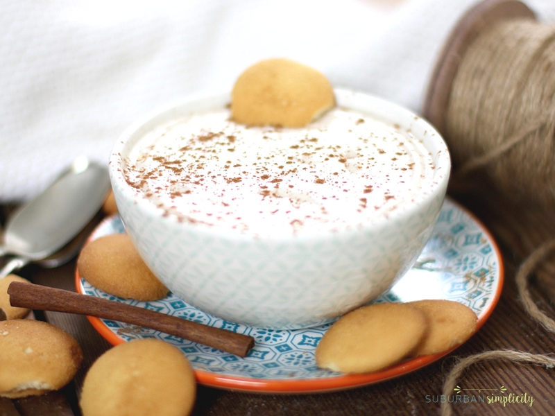 Eggnog dip in a bowl with cinnamon sprinkled on top. It's sits on a plate with vanilla wafter placed around it.