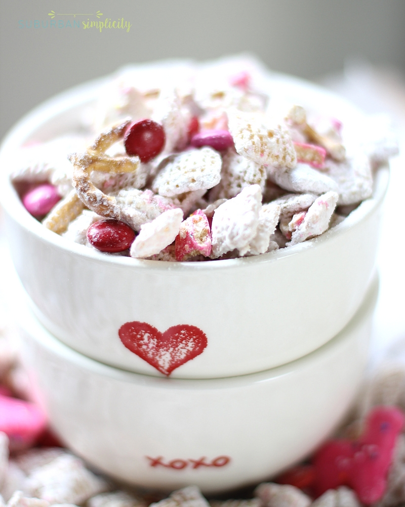 Two Valentine's Day bowl stacked with Valentine's Day Puppy Chow inside.