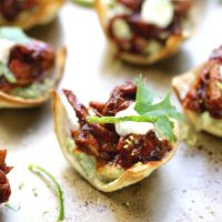 Mini Chicken chipotle tostadas on a serving platter garnished with cilantro and lime.