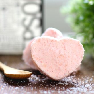 Heart shaped bath bombs next to a mixing spoon with epsom salt in the background.
