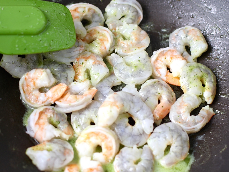 Raw shrimp cooking in a pan.