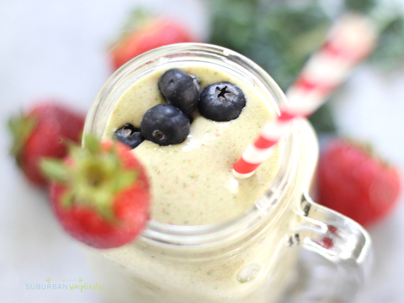 Strawberry Kale Smoothie in a mason jar with straw and strawberry garnish