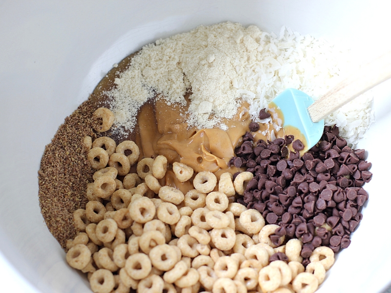 Ingredients to make Honey Nut Cheerios Protein bites in a blue bowl with a spatula in it