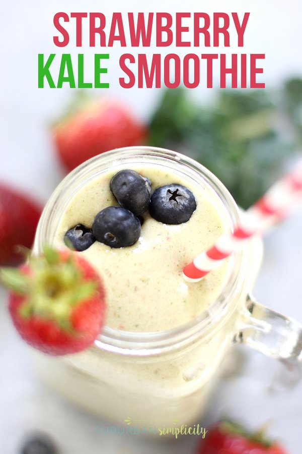 Delicious Strawberry Kale Smoothie in a mason jar with garnished with fresh strawberry and blueberries