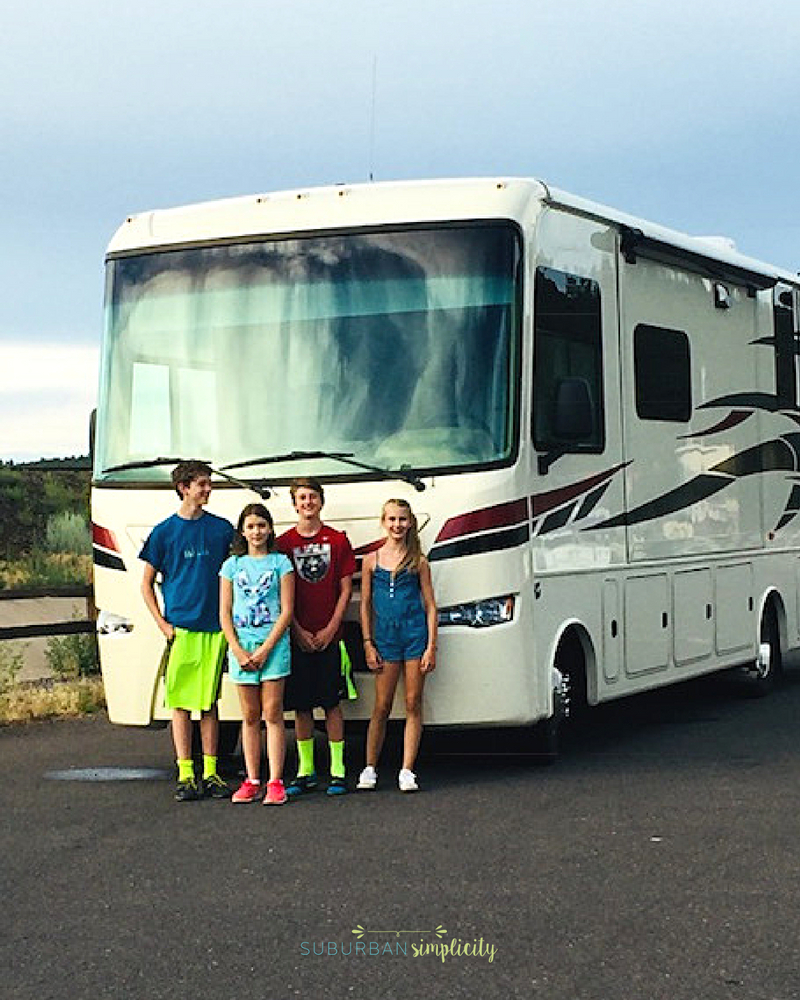 RV with kids standing in front.