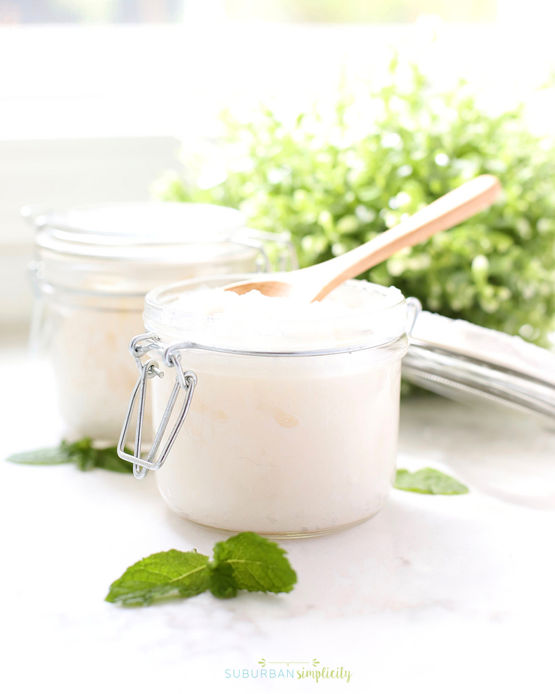 Two jars of mint sugar scrub on a counter with mint leaves in front.