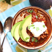Crock pot taco soup in a bowl with sour cream on top.