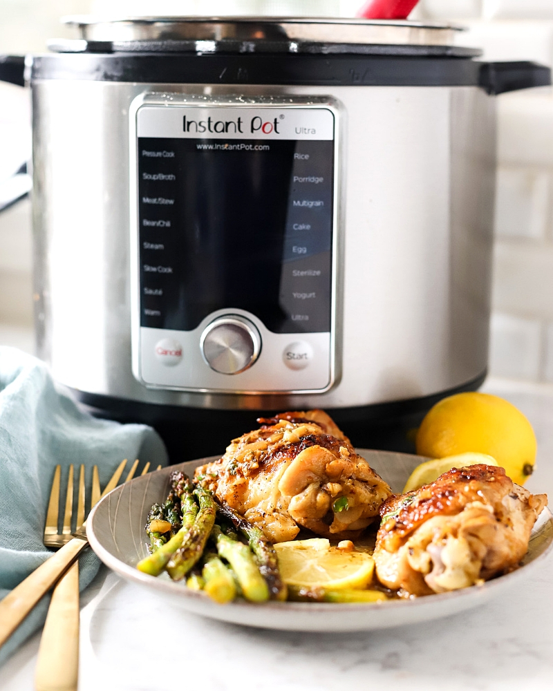 Tender Instant Pot Lemon Chicken on a plate in front of a pressure cooker