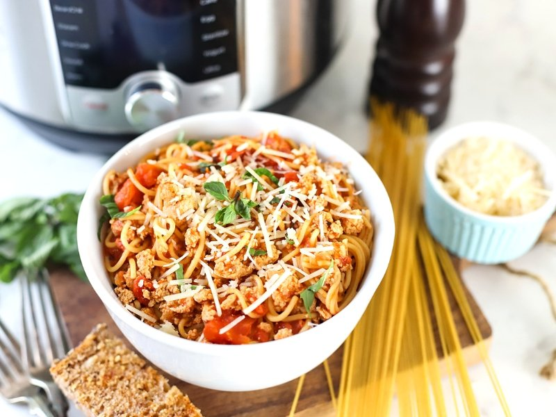 Instant Pot Spaghetti in a bowl with garlic bread.