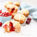 Cherry Pie Bombs on a counter with fresh cherries.