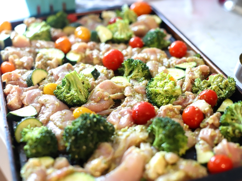 Chicken, broccoli, tomatoes, and zucchini on a baking pan.
