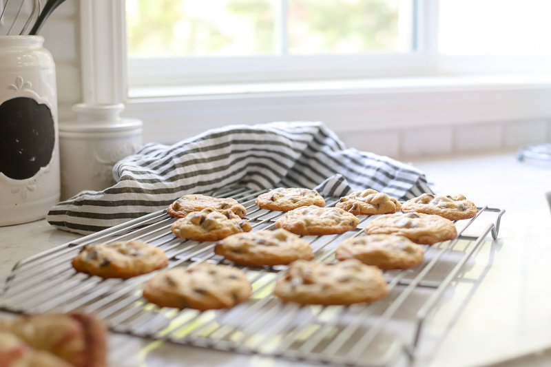 Cookies with chocolate chips cooling on a rack.