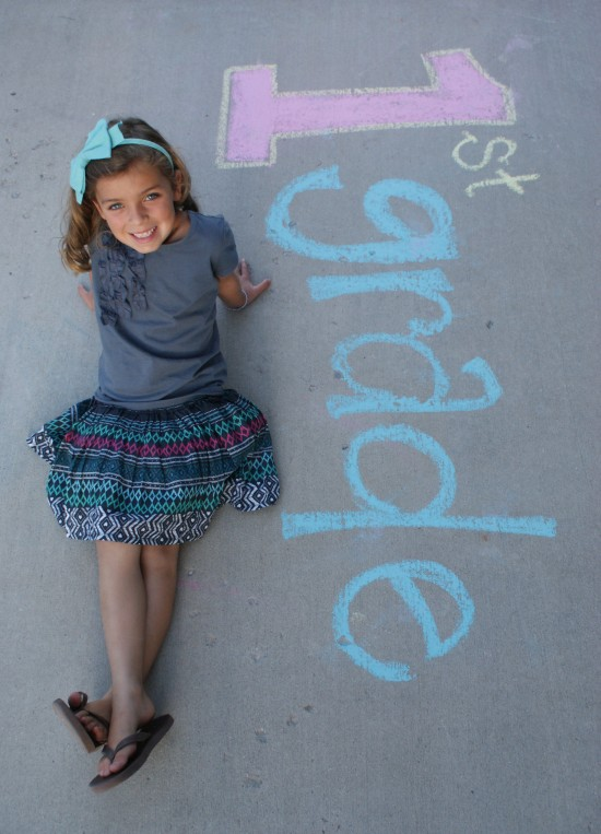 A little girl posing for a picture on the ground.