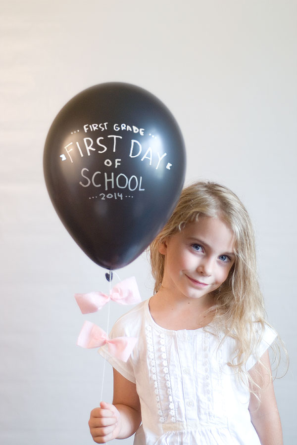A little girl posing for a picture with a balloon