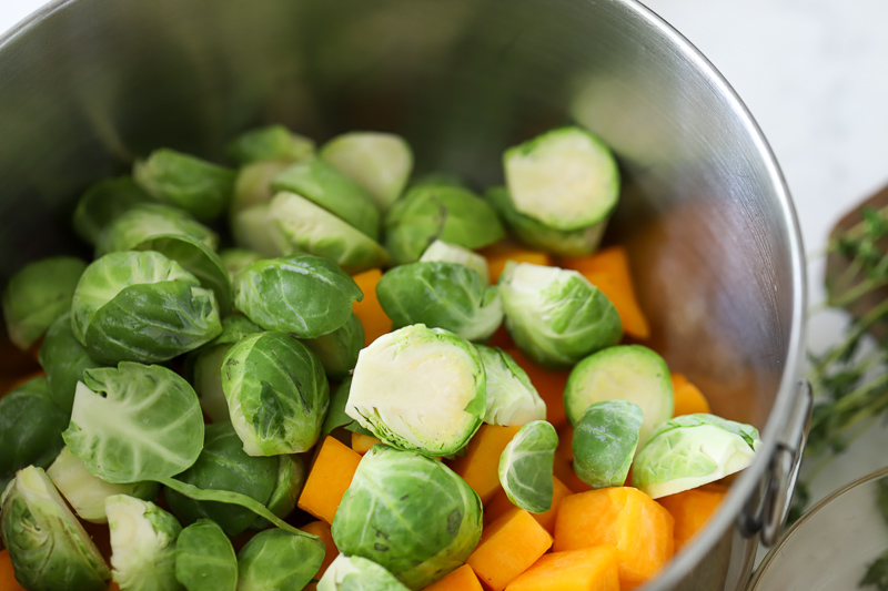 A bowl filled with cut Brussels sprouts and Squash.