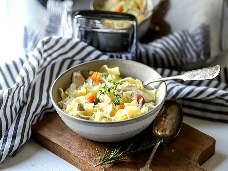 Crock Pot Chicken Noodle Soup in a bowl in front of slow cooker