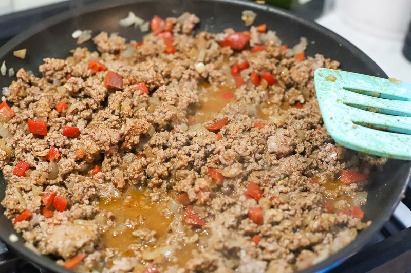 Beef and onions and peppers cooking in a pan.