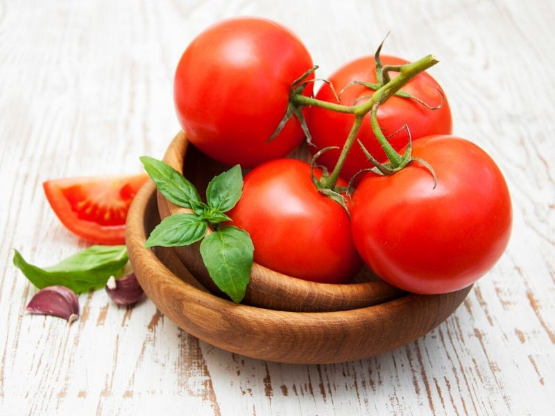 A wooden bowl filled with fresh tomatoes on a counter.