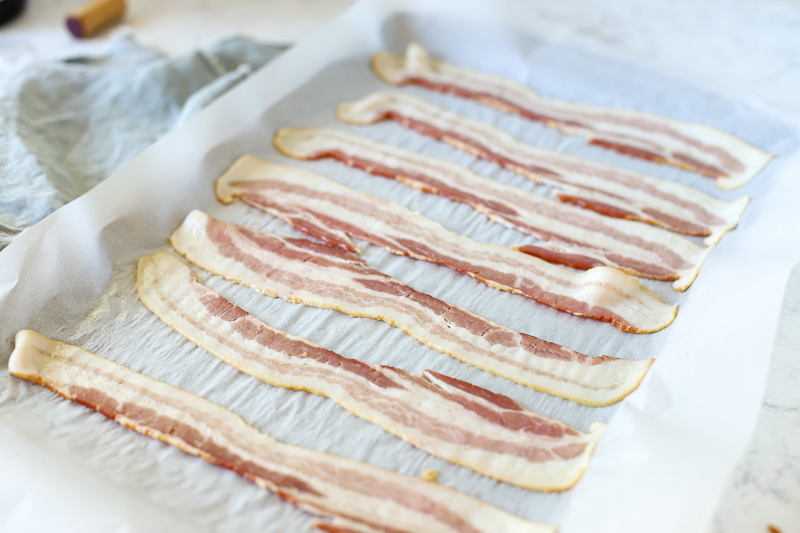 raw bacon on a baking sheet.