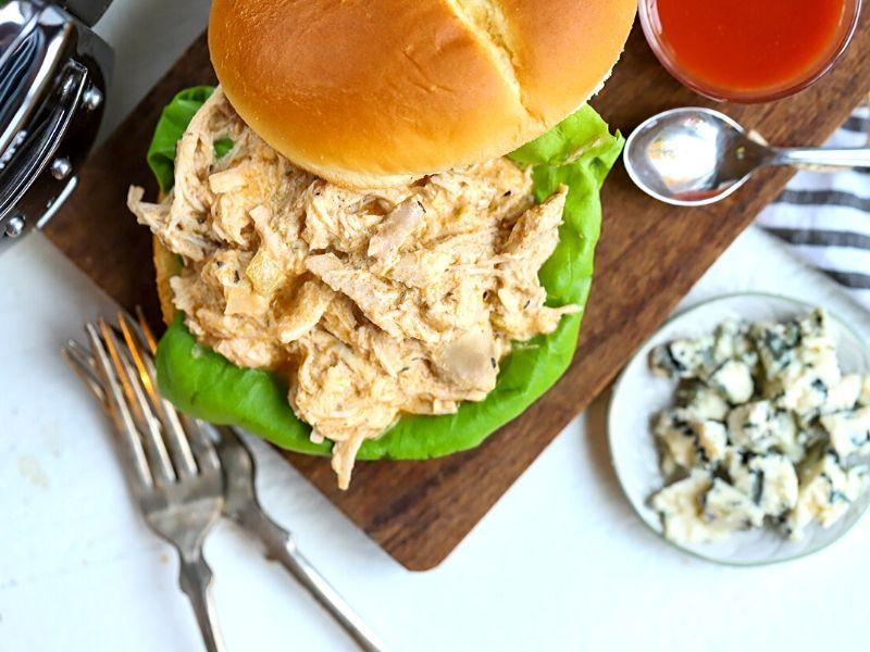 A healthier slow cooker buffalo chicken in a sandwich.