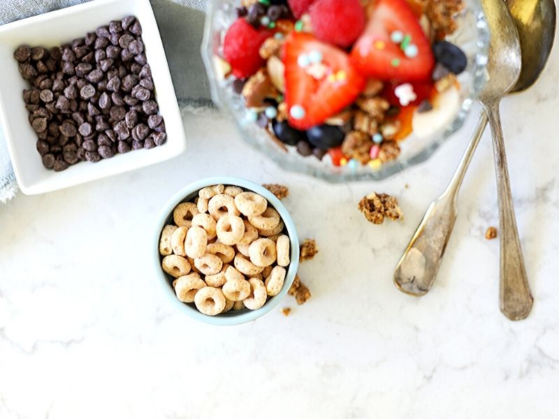 Cheerios in a bowl next to a breakfast sundae