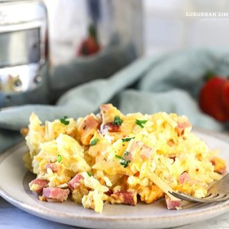 This easy Overnight Crock-Pot Breakfast Casserole is a delicious crowd-pleaser! Shredded potatoes are layered between savory ham, cheese, and eggs.