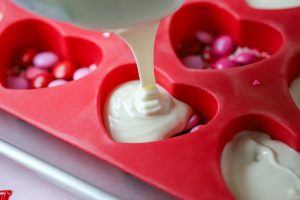 white chocolate being poured in a heart-shaped mold