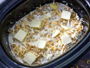 butter slices on top of macaroni in slow cooker